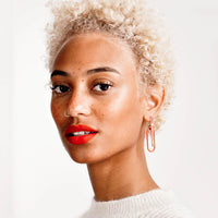 2: Model wearing sculptural brass and enamel earrings