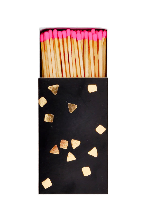 2: A black matchbox with golden flecks is slid open to reveal matchsticks with neon pink tips.