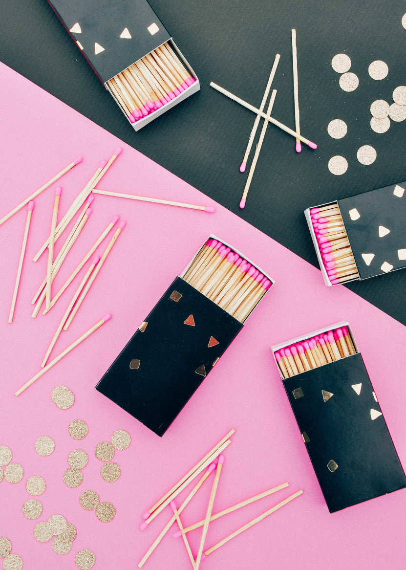 3: Three black and gold matchboxes are displayed amongst messy piles of pink-tipped matches on a black and pink surface.