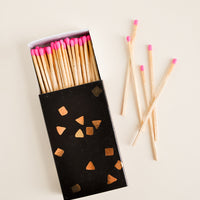 1: A black matchbox with golden flecks is slid open to reveal matchsticks with neon pink tips.