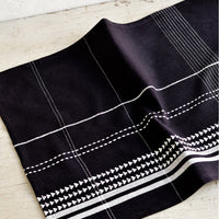 1: A black and white woven placemat on a table.