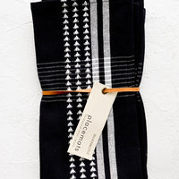 Black: A pair of folded black and white placemats with hangtag.