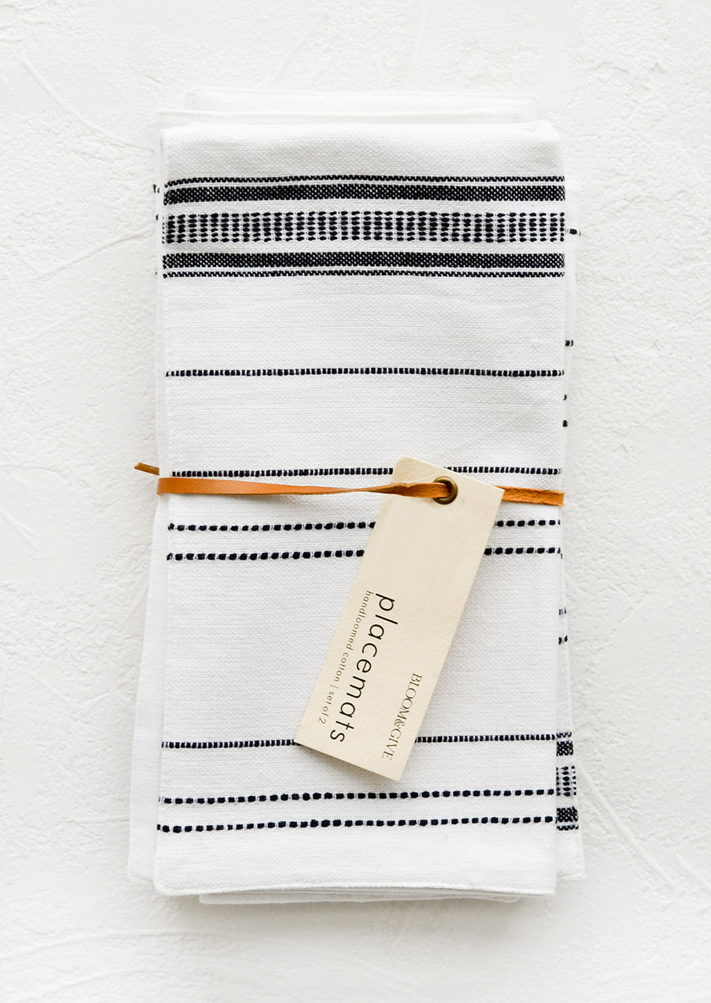 White: A pair of folded white and black placemats with hangtag.