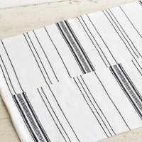5: A white and black woven placemat on a table.