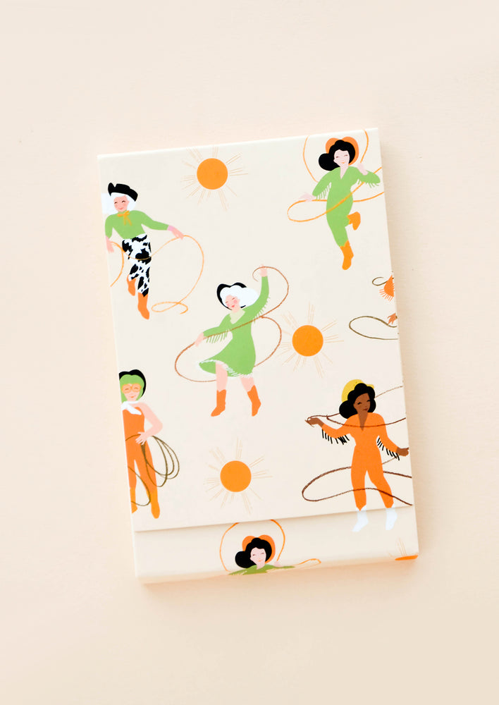 1: Covered notebook with playfully illustrated cowgirl & lasso print in green and orange