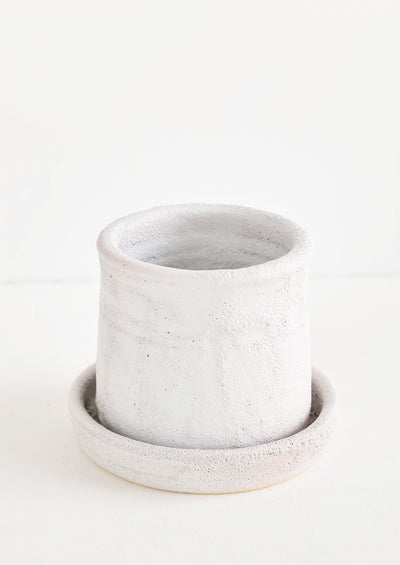 Round planter with saucer, allover heavy and crater-like texture in cool white matte glaze