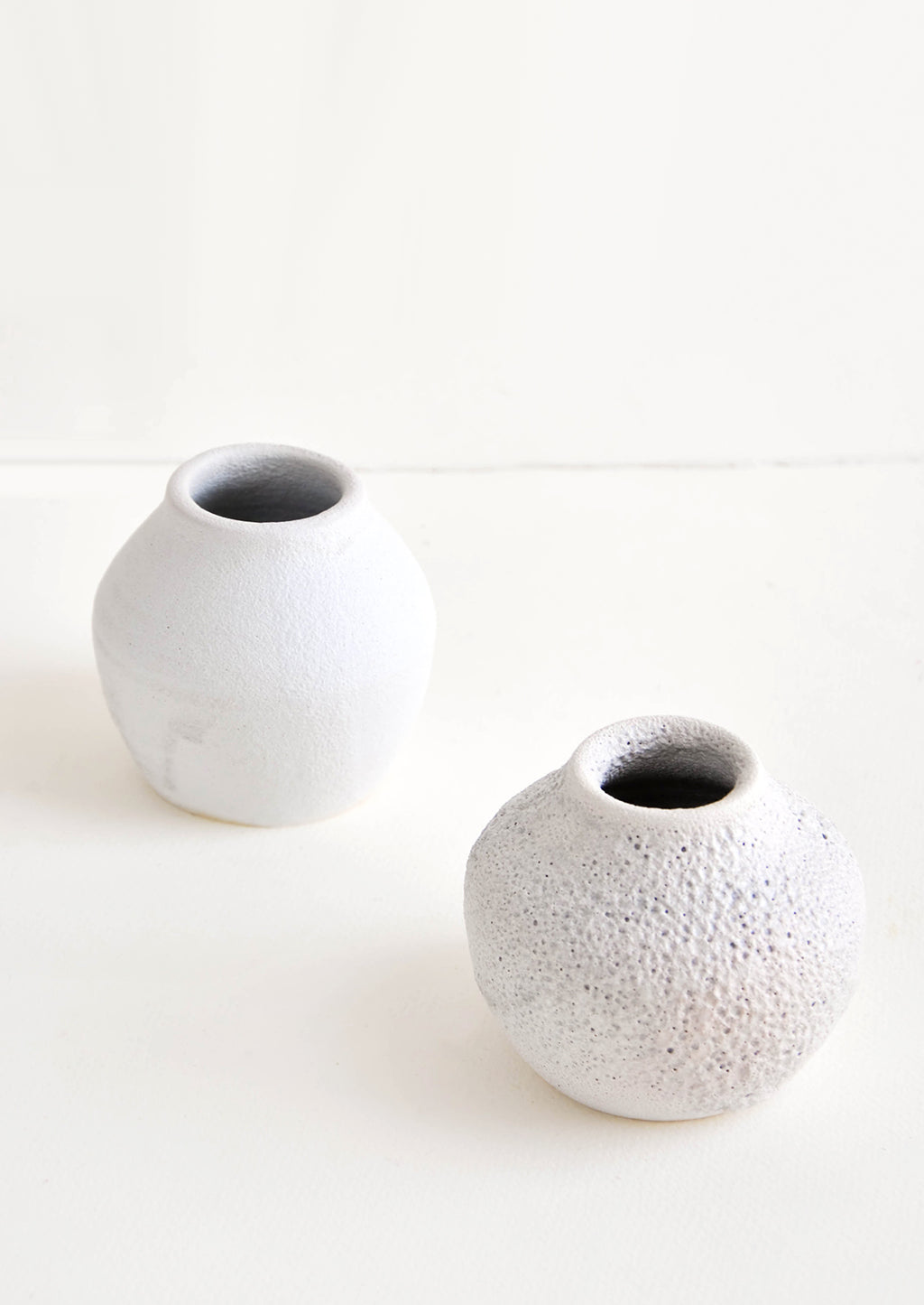 2: Small, round and wide vase with heavily textured, crater-like glaze in cool white