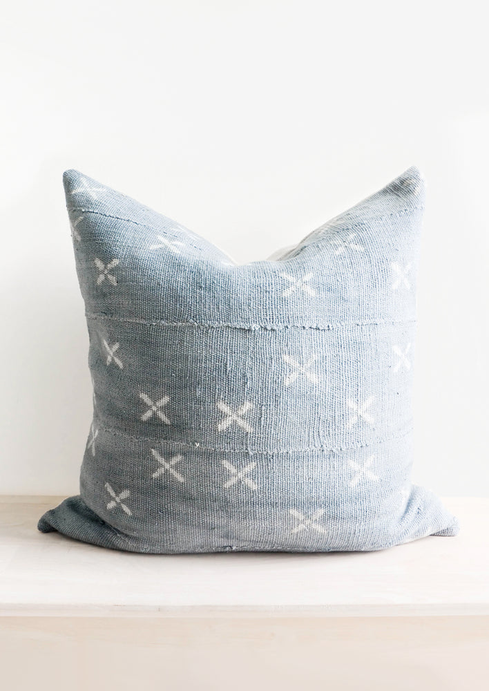 1: Square throw pillow in faded blue fabric with white X print throughout