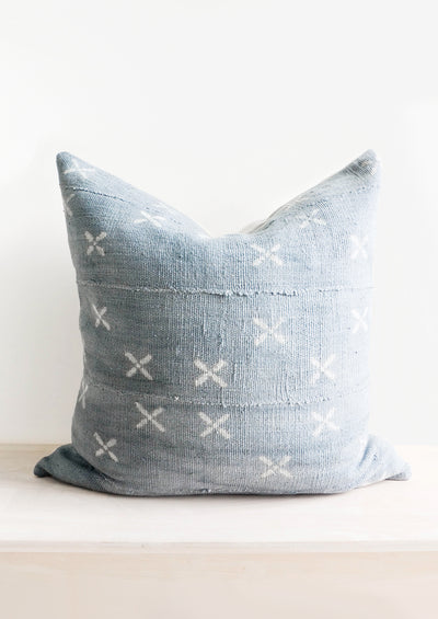 Square throw pillow in faded blue fabric with white X print throughout
