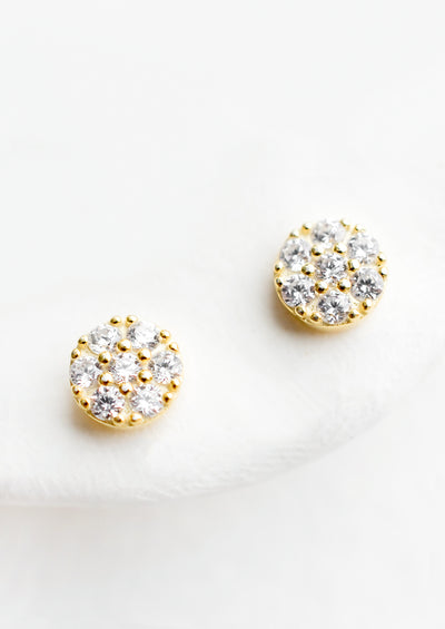 A pair of small gold circular studs with clear crystal detailing.
