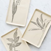 1: Rectangular ceramic trays in natural bisque color with etched black botanical drawings