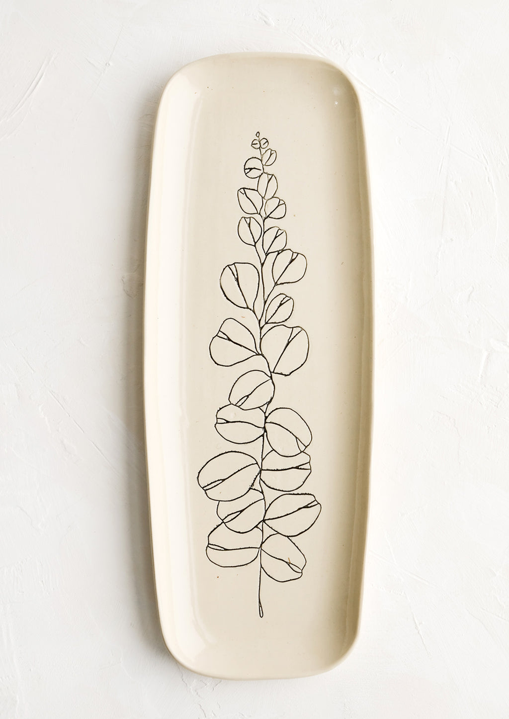 Eucalyptus: A long and skinny ceramic tray in natural bisque color with an etched black drawing of a eucalyptus branch.