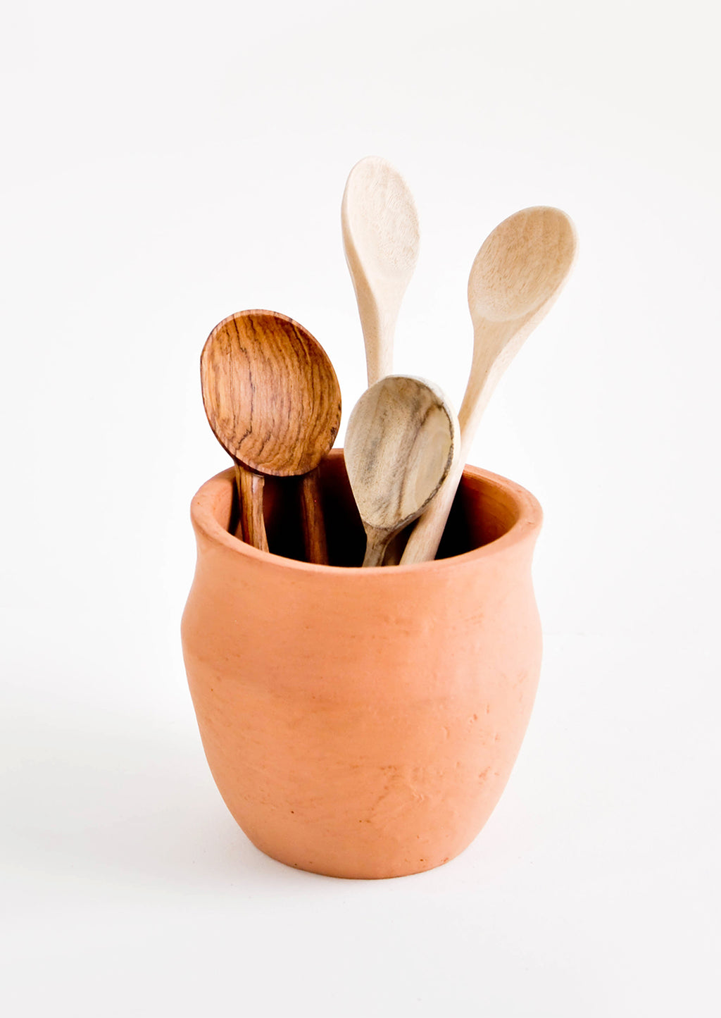 2: An orange rounded terracotta pot with curved lip holding various wooden spoons.