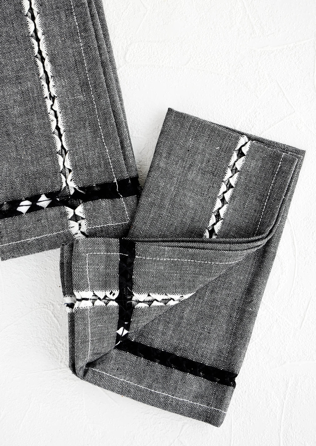 2: Pair of folded fabric dinner napkins in black chambray with geometric cutout detailing