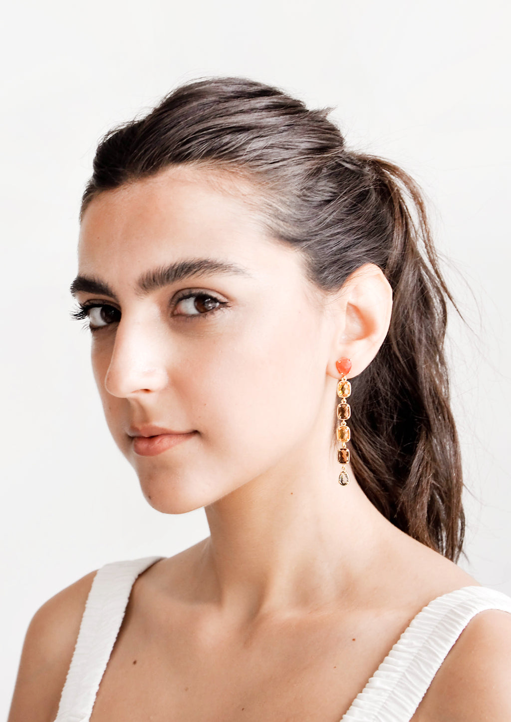 2: Model wears glass crystal drop earrings and white tank top.