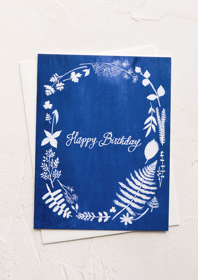 "A blue greeting card with white floral print and ""Happy birthday"" in cursive."