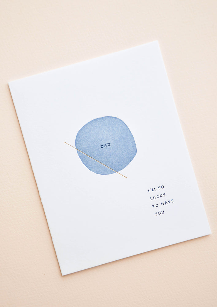 "2: White greeting card with letter press printed blue circle at center reading ""Dad"". Bottom corner reads ""I'm So Lucky To Have You""."