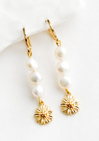 A pair of gold earrings with three pearls and a flower charm at bottom.