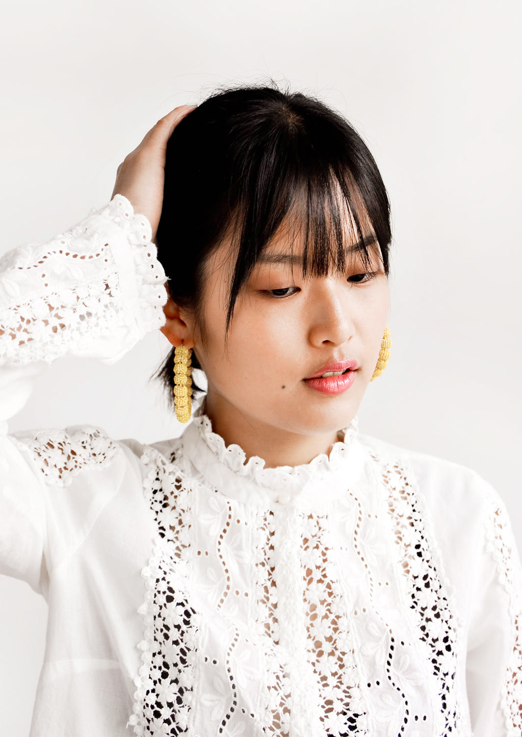 2: Model shot of woman wearing earrings and white top.