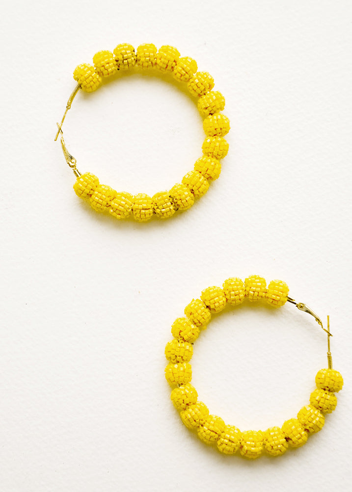 Mimosa: Hoop earrings made of small yellow beaded balls arranged in a circle.