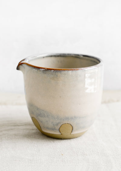 A small ceramic pitcher in mottled pastel glaze.