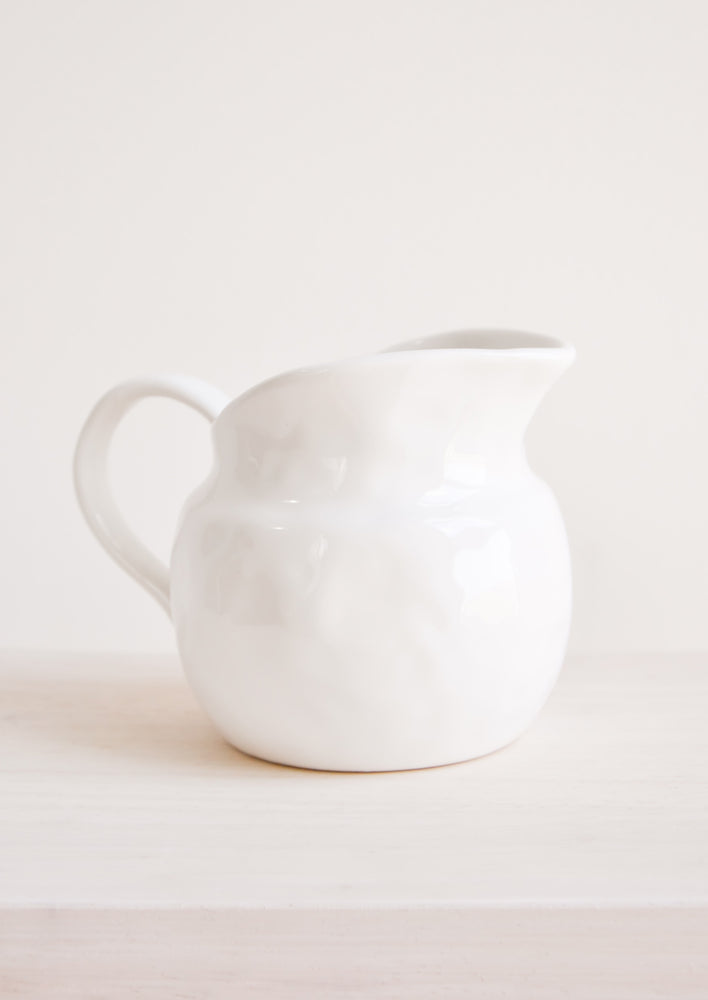 14 oz [$26.00]: Textured glossy white ceramic pitcher with round body.