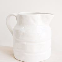64 oz [$45.00]: Large textured glossy white ceramic pitcher with curved handle.