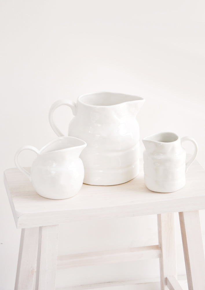 2: Trio of white ceramic pitchers in different sizes and shapes.