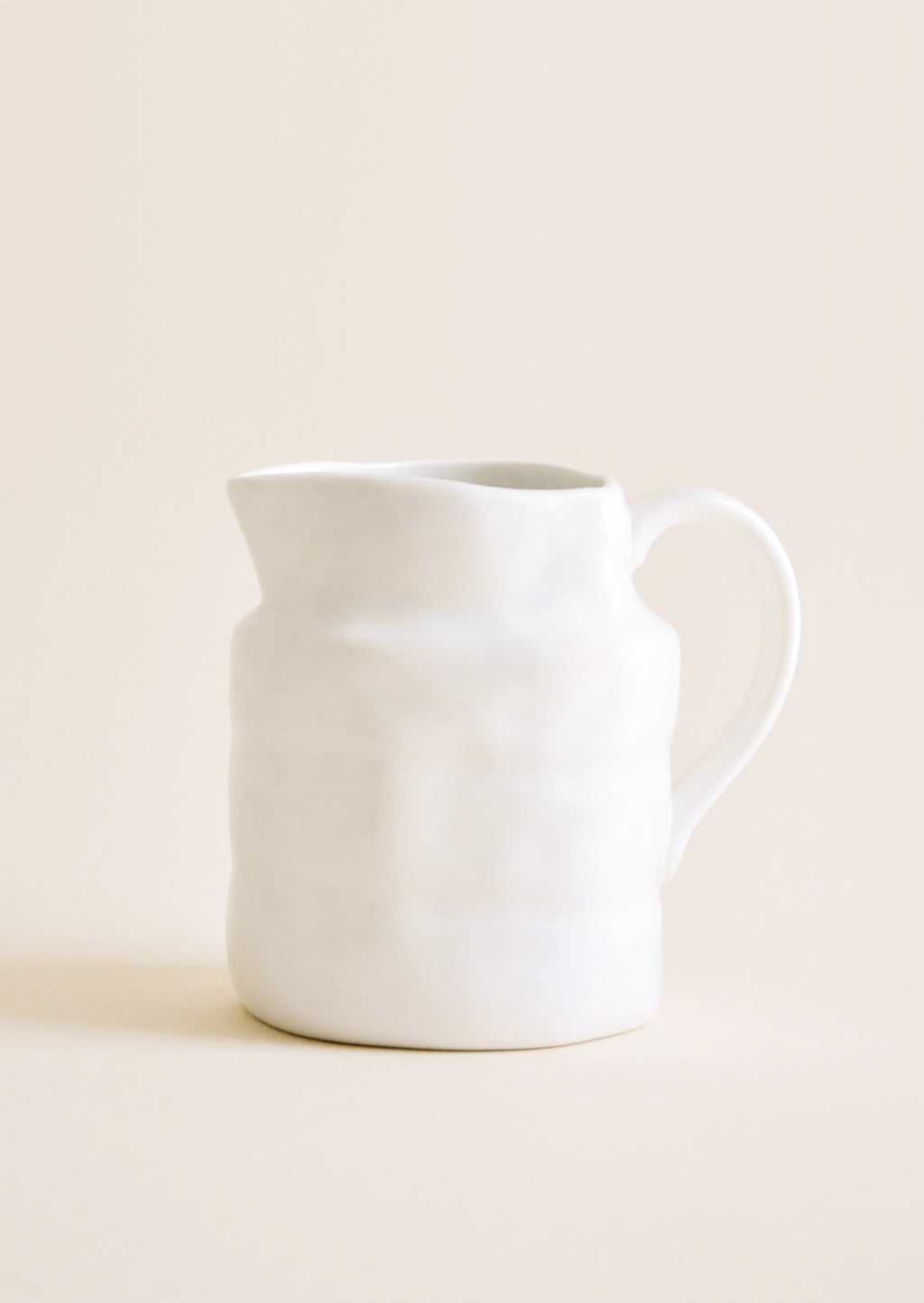10 oz [$14.99]: Textured glossy white Ceramic Pitcher with thin delicate handle.