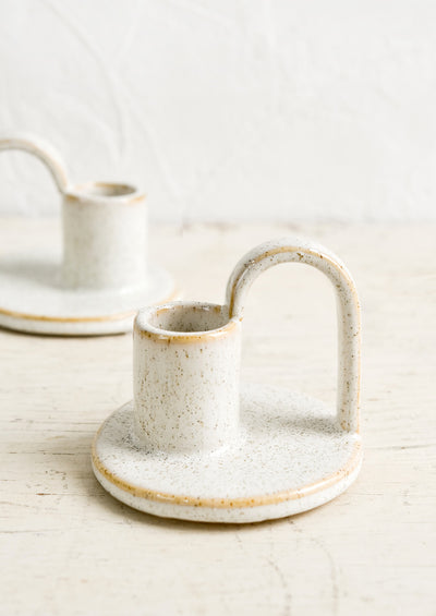Ceramic taper holders with curved handle in speckled natural glaze.