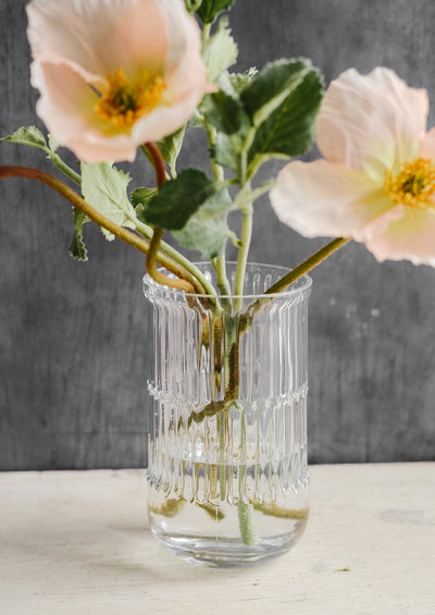 A textured clear glass vase with poppy flowers.