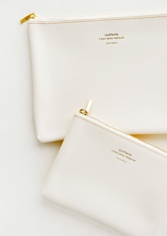 Medium and small vinyl pouches with gold zipper and crosshatch texture, in cream.