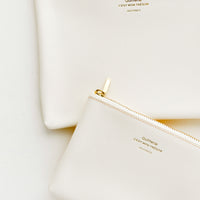 Cream / Small: Medium and small vinyl pouches with gold zipper and crosshatch texture, in cream.