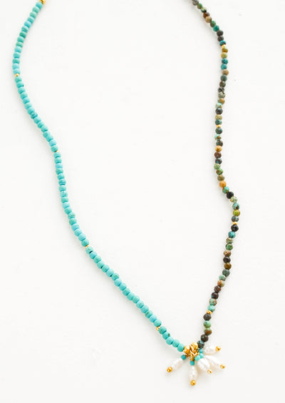 Beaded necklace with round turquoise stone beads, five freshwater pearls dangle at front and center