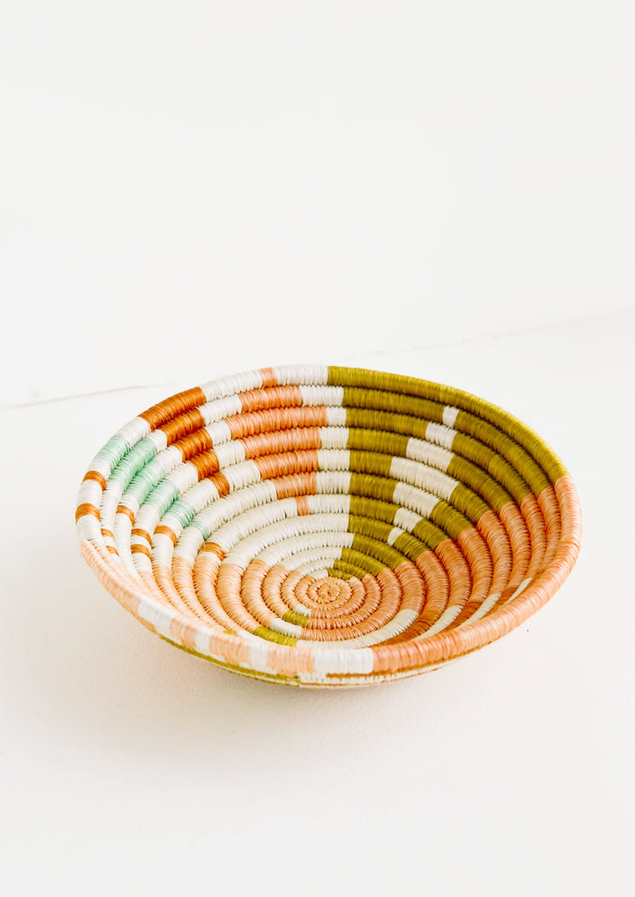 1: Shallow bowl made of woven fiber in a mix of pastel colors and geometric patterns
