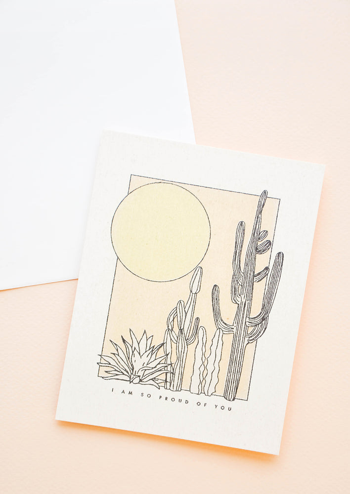 "1: A greeting card with a simple illustrated scene of cacti and the sun with the phrase ""I am so proud of you"" just below."