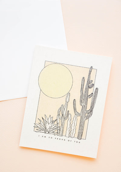 "A greeting card with a simple illustrated scene of cacti and the sun with the phrase ""I am so proud of you"" just below."