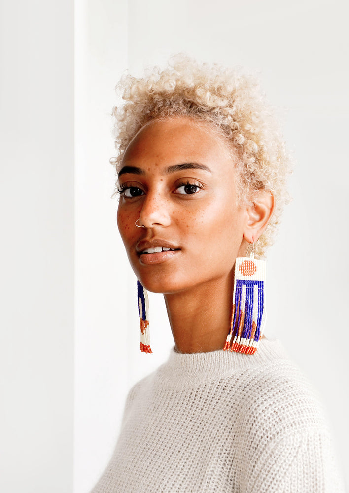 1: Model wears long fringe earrings with blue details.