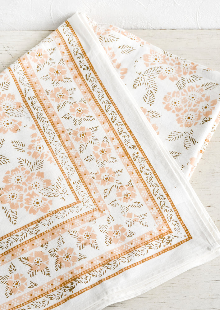 1: A block printed tablecloth with peach and brown floral print.