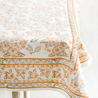 2: A block printed tablecloth with peach and brown floral print.
