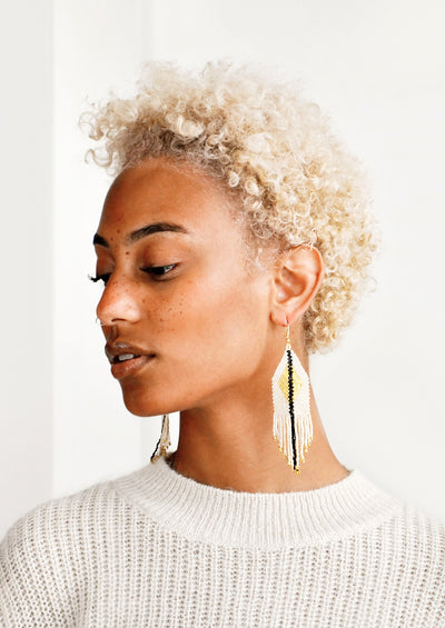 Model wears ivory fringe earrings with black stripe down the center.