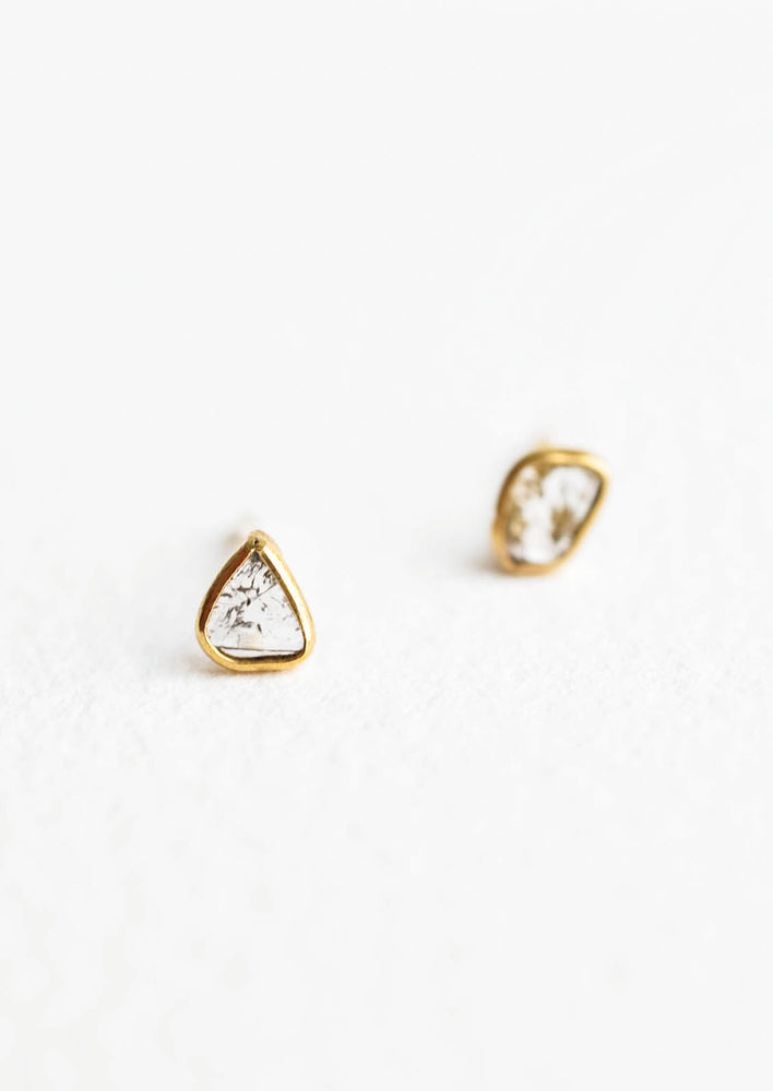 Organically shaped stud earrings with small diamond slice surrounded by brass metal trim