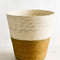 Ochre: A conical shaped storage basket made from woven palm leaf in ochre & natural color way.
