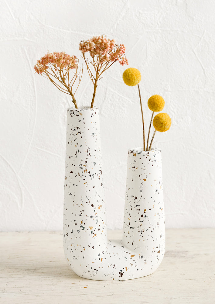 1: A u-shaped tubular vase made from white concrete with terrazzo flecks.