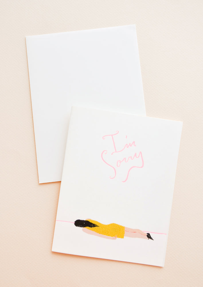 "1: Greeting card with illustration of girl in yellow dress, laying face down on ground. Words ""I'm Sorry"" above in pink script."