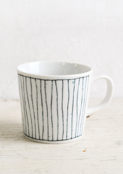 A glossy white ceramic mug with hand-drawn line pattern in dark indigo.