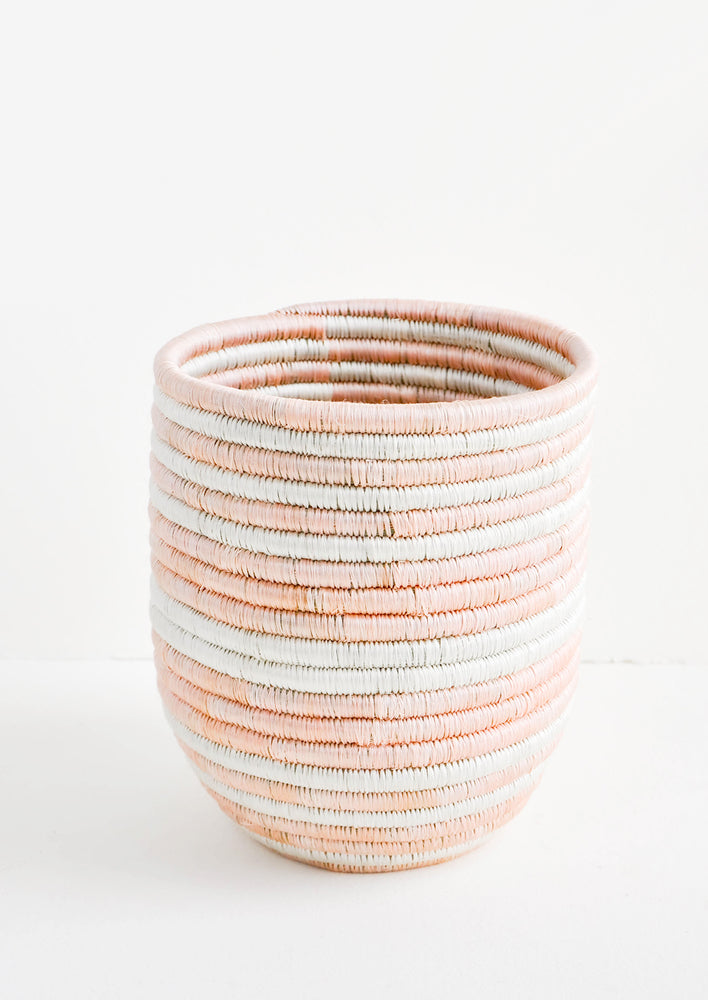 1: Elongated, round basket woven out of dyed sweetgrass in alternating light pink and white stripes.