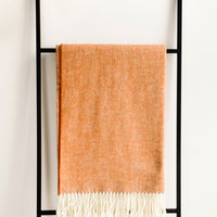 3: Soft blanket in colored herringbone weave. Ivory tassel trim at ends. Displayed hanging on a ladder.