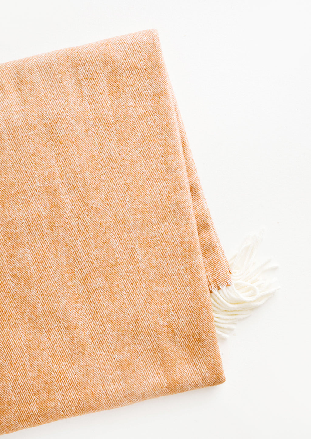 Copper: Soft blanket in copper colored herringbone weave. Ivory tassel trim at ends.