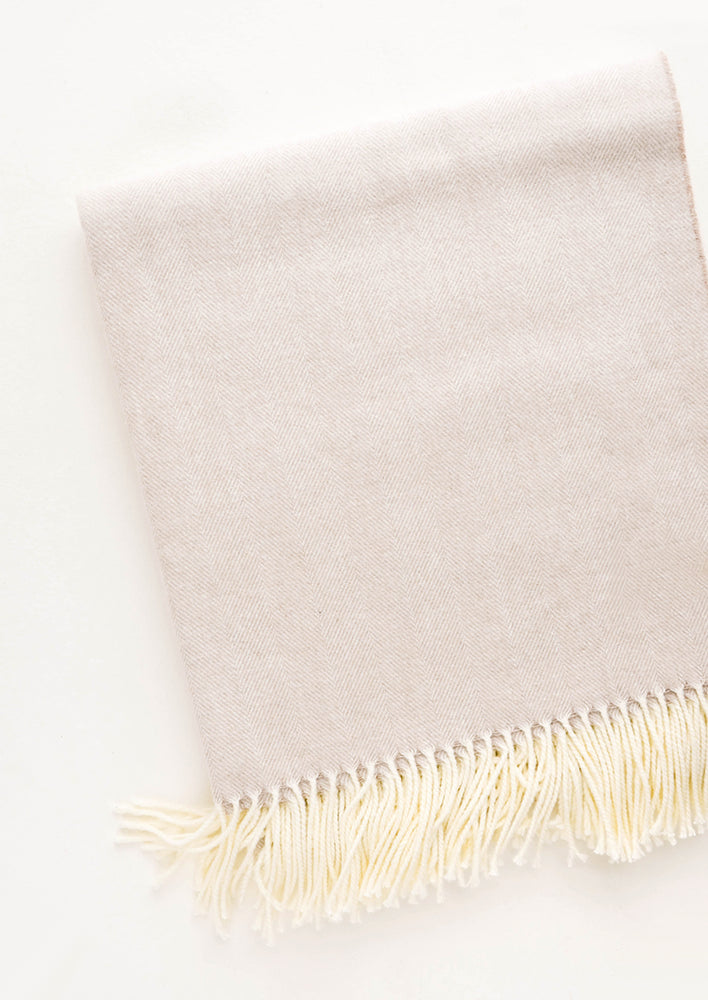 Latte: Soft throw blanket in fine herringbone weave and ivory tassel trim. Soft tan color.